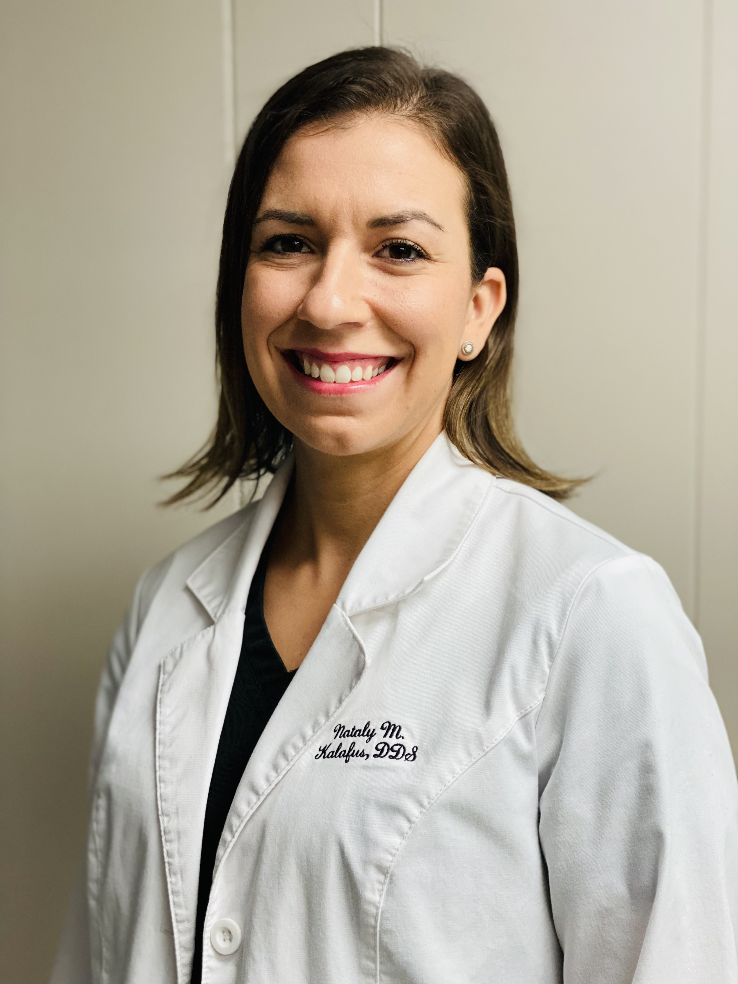 Doctor Nataly Kalafus. She is smiling broadly, and is a Latin woman with dark eyes, shoulder-length brown hair, and diamond stud earrings. She is wearing a lab coat and a black shirt.